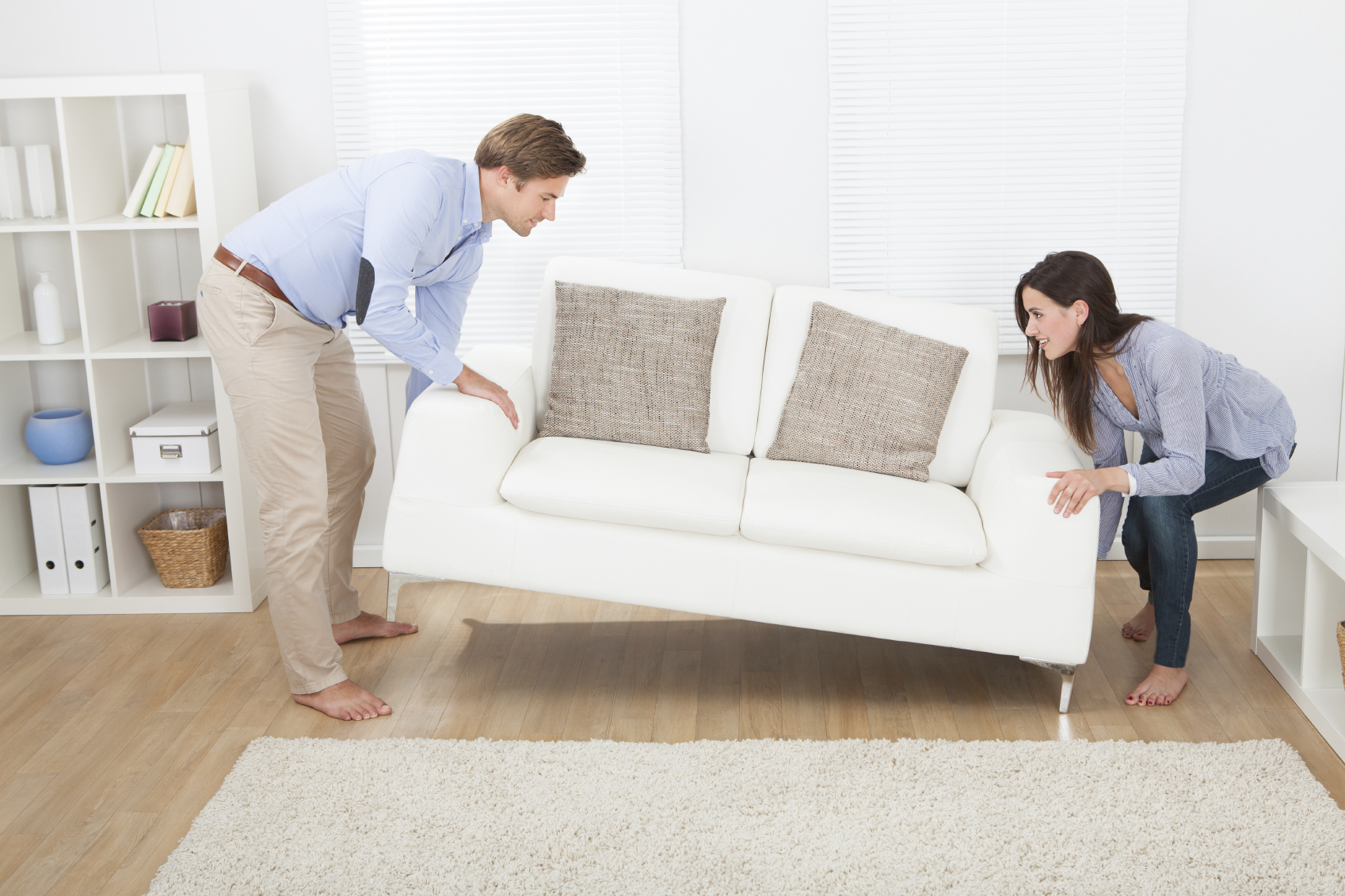 Happy Couple Placing Sofa In Living Room